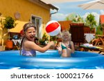 Children - they are sisters - playing in water with a ball in the garden in front of the house