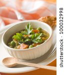 Minestrone soup with celery, carrots, onions, green beans and zucchini, selective focus - stock photo