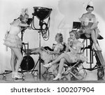 Women in costumes with movie equipment - stock photo
