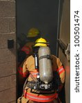 Small photo of fire fighters crawling through a smoky structure with fire hose and scba