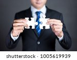 Small photo of Businessman hands connecting puzzle pieces representing the merging of two companies or joint venture, partnership, Mergers and acquisition concept.
