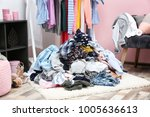 pile of clothes on floor indoors | Shutterstock . vector #1005636613