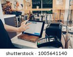 Stock photo closeup shot of caucasian cashier hands seller using touch pad for accepting client customer 1005641140