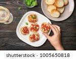 woman holding tasty bruschetta... | Shutterstock . vector #1005650818