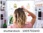 rear view of a confused woman... | Shutterstock . vector #1005702643
