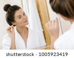 woman cleansing her ears with a ... | Shutterstock . vector #1005923419