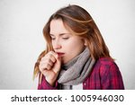 unhappy female coughs as caught ... | Shutterstock . vector #1005946030
