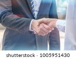 woman is shaking hand with... | Shutterstock . vector #1005951430