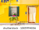 Yellow House With Flowers And...