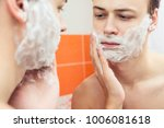 Small photo of close up of young man looking to mirror and shaving beard with manual razor blade at home bathroom, Reflection of guy ready to shave through shave foam, concept of men skin care, hygiene, grooming