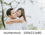 Stock photo happy young asian couple in love having a good time and embracing in the park 1006211680