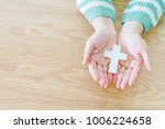 Small photo of Woman hands holding a holy cross on wooden table.Christian, Christianity, Religion background.