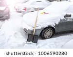 clearing the snow from the car... | Shutterstock . vector #1006590280