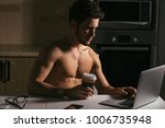 physically fit man using laptop ... | Shutterstock . vector #1006735948