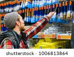 a young man chooses paintbrush... | Shutterstock . vector #1006813864