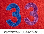 Small photo of Number thirty-three blue purple color over a red background. Anniversary