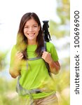 Hiker portrait - hiking woman standing smiling happy in forest clearing. Beautiful sporty healthy lifestyle image of young fresh multiracial hiker woman on trek. - stock photo