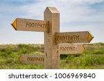 Small photo of All roads lead to Rome - Sign: Footpath, pointing in all directions, seen in Tide Mills near Seaford, East Sussex, UK