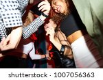 Small photo of Low angle view at crowd of excited dancing people in nightclub, focus on smiling beautiful girls, shot with flash
