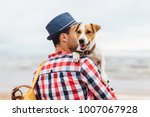 Stock photo small beautiful dog on owner s hands stylish young male model dressed in fashionable clothes 1007067928