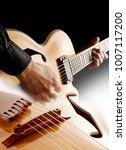 Small photo of hands of guitarist playing handmade custom jazz guitar