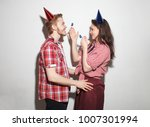 Small photo of young modern cocky guy and girl have fun, laughing in party caps with pipes, isolated over white