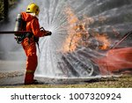 fire fighter hosing water to ... | Shutterstock . vector #1007320924