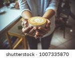 woman hand holding coffe cup in ... | Shutterstock . vector #1007335870