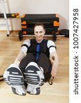 Small photo of Smiling caucasian woman makes abdominal muscles exercises in gym. She wears a suit with electrodes. Electric muscle stimulation purposed to increase effectiveness of training. Vertical shot