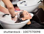 beautiful brunette washes hair... | Shutterstock . vector #1007570098