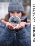 Small photo of closeup of young woman outdoors holding a glass sphere