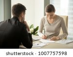 Small photo of Satisfied with loan terms woman singing contract when sitting at desk in front of male bank employee at office. Millennial female applicant accepting employers offer and putting signature in agreement
