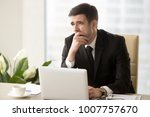 Small photo of Tired businessman covering his mouth with hand when yawning at desk in office. Office worker feeling lack of sleep during work day, suffering of fatigue or overwork, languishing through boring work