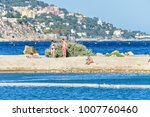 Small photo of CAP D'AIL, FRANCE - JUNE 29, 2017: Daylight view to people walking and sun tanning on sand near rocks. Buildings and trees on background. Negative copy space, place for text. Cap d'Ail, France