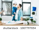Small photo of Thirst for knowledge. Cute little boy in a white hard hat asking his father questions about the construction blueprint while the man holding him and finishing up the work