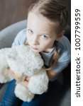 Being alone. Unsmiling blue-eyed little girl hugging and holding her teddy bear while sitting in the armchair - stock photo