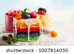 Small photo of Various slices of cakes on a white tray: rainbow cake, raspberry cake and almond cake. Sweets decorated with fresh berries and flowers for holiday