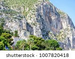Small photo of Daylight view from bottom to green mountains full of small trees. Bright blue clear sky. Negative copy space, place for text. Cap d'Ail, France