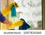 female hand in yellow gloves... | Shutterstock . vector #1007824360