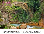 """Small photo of NEDA CANYON, GREECE. Old stone arched bridge over Neda river, in Neda canyon, at the """"borders"""" of Messinia & Ileia prefectures, Peloponnese."""