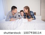 mom dad and son lie on the bed... | Shutterstock . vector #1007938114