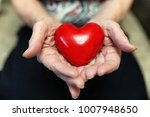 Small photo of elder woman holding heart shape in a hands