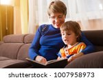 grandmother reading a tale to... | Shutterstock . vector #1007958973