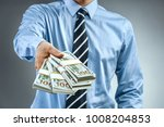 man in blue shirt holding cash... | Shutterstock . vector #1008204853