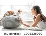 Stock photo beautiful young woman with cute cat near window at home 1008235030