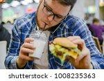 man eat burger drink milk shake ... | Shutterstock . vector #1008235363