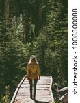 Small photo of Woman walking on bridge way over river alone Travel Lifestyle emotional concept forest on background Summer journey vacations outdoor