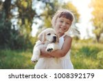 Stock photo little girl with a golden retriever puppy a puppy in the hands of a girl 1008392179