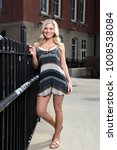 Small photo of Stunning young blonde woman poses in a black and white sundress or romper near a cast iron fence