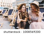 Small photo of Irresistible laughing girl listening friend's joke and drink champagne. Two stunning women spending time together and recollect funny stories while sitting outdoor with goblets.